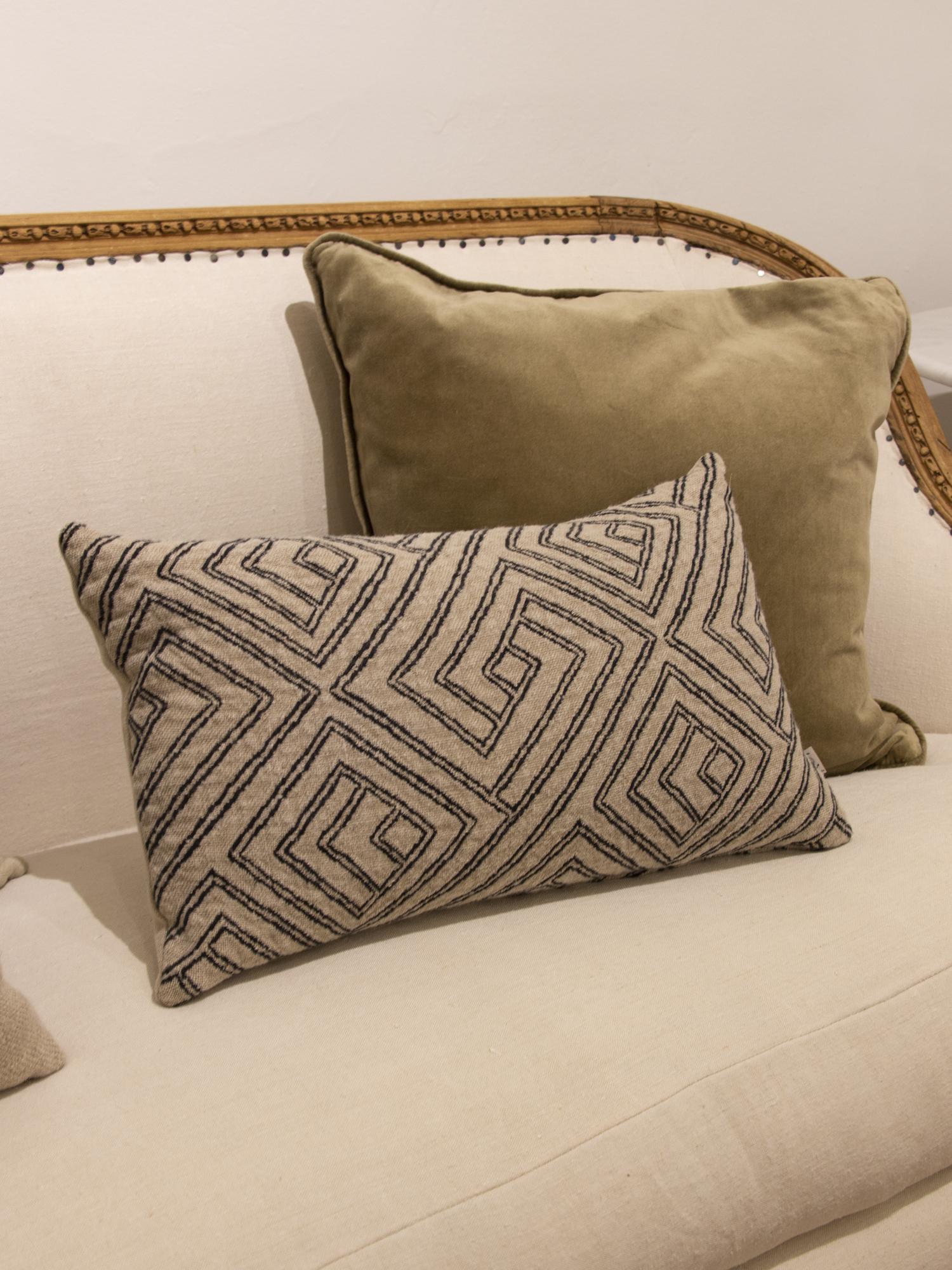 Cojín rectangular de lino con estampado geométrico en color crema y negro y parte trasera en color crema.