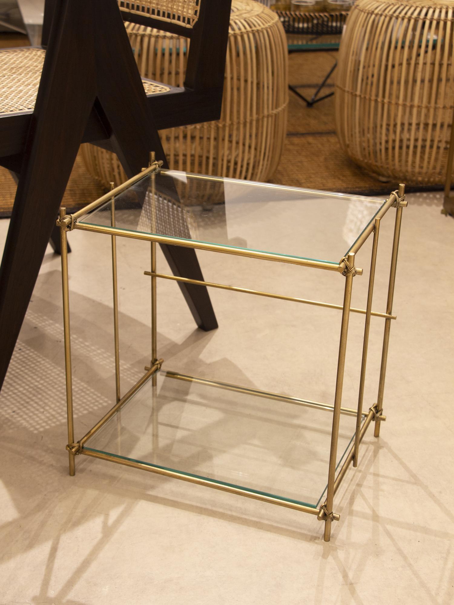 Mesa auxiliar rectangular con dos baldas en cristal y estructura en metal dorado. Con detalles en las esquinas.